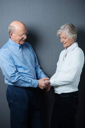 clasping: Romantic senior couple sharing a tender moment clasping hands as they stand facing each other smiling with love Stock Photo