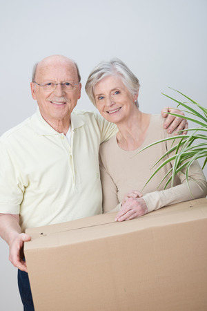 moving in: Elderly couple moving house standing arm in arm with a brown cardboard carton smiling happily in anticipation of a new beginning Stock Photo