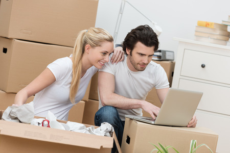 removals: Young couple moving house checking their email sitting amongst cardboard boxes balancing a laptop on top of one of them