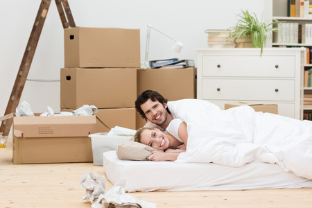 Happy couple sleeping on the floor in their new home lying on a mattress in the living room surrounded by cardboard boxes photo