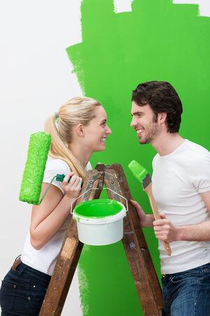 絵画、新しい明るい緑に立っている家ローラとペイント ブラシを保持するとお互いに幸せそうに笑って木製脚立に幸せな若いカップル