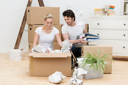removals: Happy young couple unpacking in their new home kneeling on a bare wooden floor unwrapping items from a large brown cardboard box