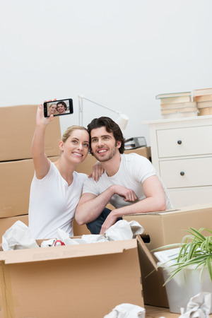 Happy young couple taking a self-portrait on a mobile phone as they unpack a brown cardboard carton in their new home photo