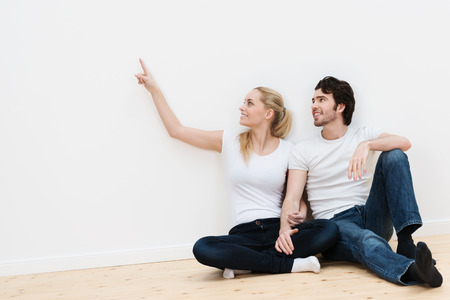 Joven pareja en su nueva casa sentado en el suelo de madera al descubierto en una habitación vacía apuntando y visualizar hacia dónde van a colocar sus posesiones