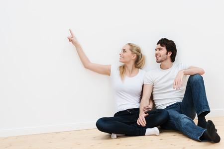 pareja en casa: Joven pareja en su nueva casa sentado en el suelo de madera al descubierto en una habitación vacía apuntando y visualizar hacia dónde van a colocar sus posesiones