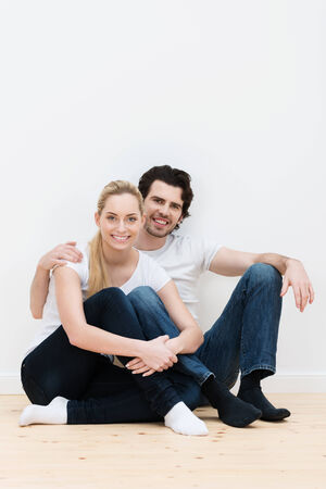Happy contented couple in their new home sitting on the bare wooden floor in their socks smiling in an affectionate embrace, with copyspace on the wall above
