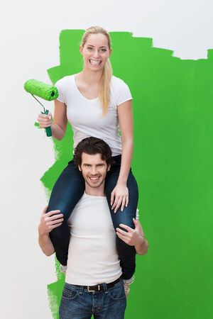 Smiling woman getting a piggy back from her husband riding on his shoulders as she paints a high wall green with a roller while decorating their new house photo