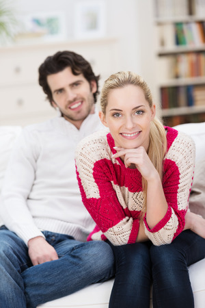 Smiling beautiful young blond woman relaxing at home with her husband sitting leaning forwards on a sofa looking at the camera with a friendly smile