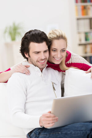 Stylish attractive couple using a tablet computer smile happily as they read information on the screen while relaxing in their living room photo