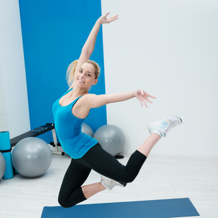 knees bent: Beautiful happy woman leaping in a gym in a graceful pose with her knees bent and arms outstretched against a backdrop of pilates gym balls