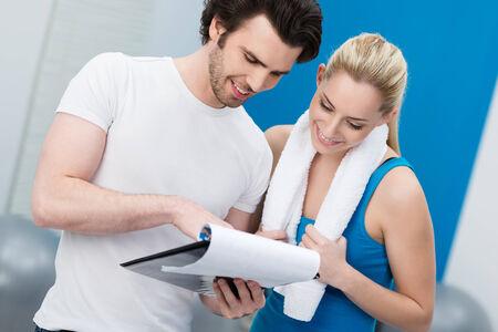 aide � la personne: Jeune femme parlant � son entra�neur de fitness dans la salle de gym souriant comme ils consultent un presse-papiers tracer ses progr�s