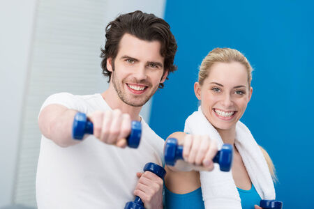 Motivated attractive young couple working out with dumbbells standing side by side giving the camera a friendly smile photo