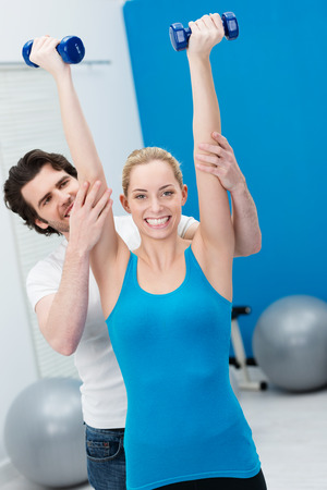 above head: Enthusiastic beautiful woman working out in the gym with the aid of a handsome male fitness instructor raising her dumbbells above her head and extending her arms Stock Photo