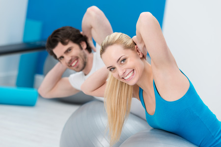 Young couple working out in a gym doing Pilates exercises together toning and strengthening their bodies turning to smile at the camera