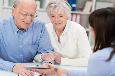 Glimlachend bejaard paar ontvangen financieel advies van een vrouwelijke makelaar die toont ze een rekenmachine