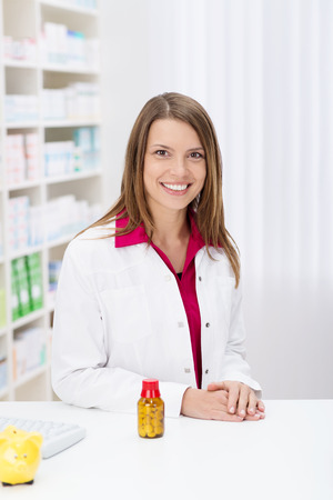 Beautiful friendly female pharmacist standing behind the counter in the pharmacy with a bottle of tablets smiling at the camera photo