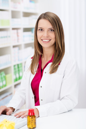 Attractive pharmacist with a lovely smile standing working on the computer behind the counter in the pharmacy photo
