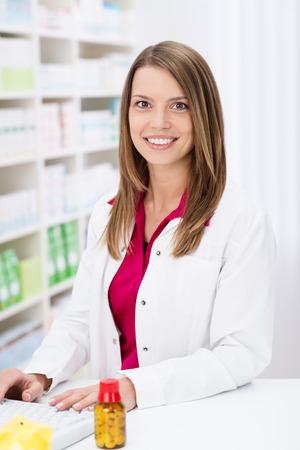 Farmacéutico atractiva con una sonrisa encantadora de pie trabajando en el equipo detrás del mostrador de la farmacia