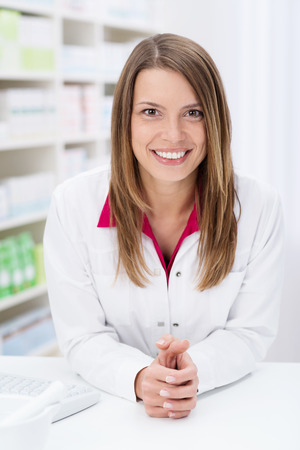 Friendly female pharmacist leaning on the counter and smiling at the camera as she waits for patients in the pharmacy photo