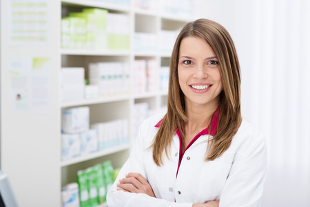 薬局で腕を組んで立っている素敵なフレンドリーな笑顔で自信を持って若い女性薬剤師 写真素材