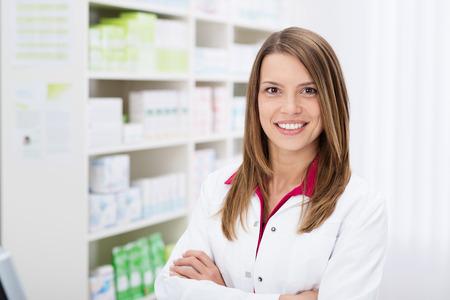 Vertrouwen jonge vrouwelijke apotheker met een mooie vriendelijke glimlach staan met gevouwen armen in de apotheek