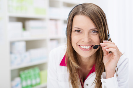 Smiling pharmacist chatting to a patient on a headset as she stands in front of the shelves in the pharmacy giving friendly advice
