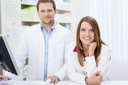 leans: Two confident young pharmacists at work with the man working on the computer as the woman leans forwards over the counter with a smile