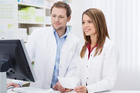 Dos farmacéuticos que cumplen una receta que tuvo lugar en la mujer joven de la mano de un verifican la información sobre el monitor de la computadora juntos