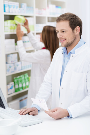 Handsome young male pharmacist checking a prescription on the computer with his female colleague checks supplies behind him photo