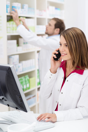 Pretty young pharmacist chatting on the phone as she checks information on the computer while a male colleague works in the background