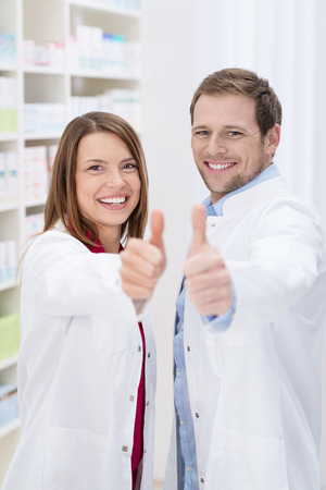 Two successful pharmacists with big happy smiles giving a thumbs up of approval as they stand together in their white la coats in the pharmacy photo