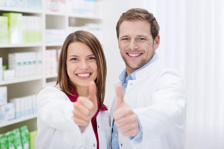 Dos farmacéuticos jóvenes motivados dando señal de los pulgares para arriba de aprobación mientras que sonríen a la cámara