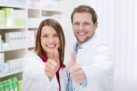 Two motivated young pharmacists giving a thumbs up of approval as they smile at the camera