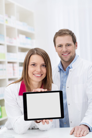 Smiling attractive young female pharmacist displaying a blank tablet with the screen to the camera watched by a male colleague photo