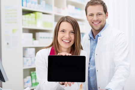 Happy vrouwelijke apotheker doet een promotie weergave van het lege scherm van een tablet-pc naar de camera als ze staat in de apotheek met een mannelijke collega