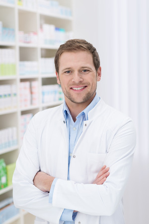 Farmacéutico guapo confidente con una sonrisa de pie con los brazos cruzados en la farmacia