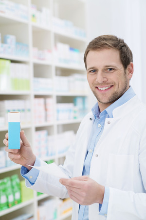 fulfilling: Smiling pharmacist holding a blank box of medication as he stands at the shelves in the pharmacy fulfilling a prescription