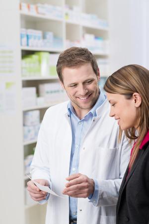 Farmacéutico de sexo masculino guapo cómodo que explicar algo sobre una receta a un paciente de la mujer