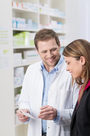 Friendly handsome male pharmacist standing explaining something on a prescription to a woman patient photo