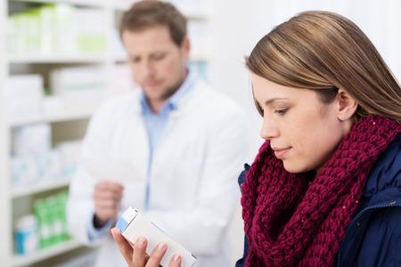 dispense: Mujer que lee la informaci�n en un cuadro de la medicaci�n como ella est� en la farmacia a la espera de que el farmac�utico para dispensar su receta Foto de archivo