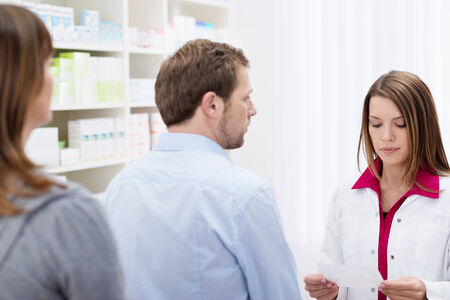 Pharmacist assisting a customer at the head of a queue as she reads his prescription photo