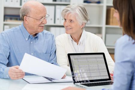 Ouderen paar in een vergadering met een adviseur een document bespreken als ze kijkt over het bureau in haar kantoor