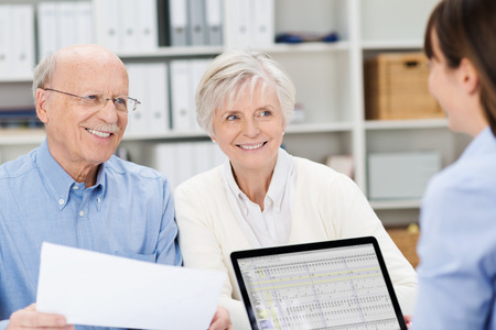 oldage: Smiling senior couple meeting with a broker in her office sitting close together holding paperwork and listening to her speak Stock Photo
