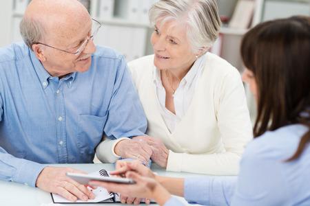 agente comercial: Abrazar pareja de ancianos en una reunión de negocios de la mano, ya que hablar de una propuesta presentada por su agente Foto de archivo