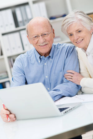 Senior sitting together at a desk in an office couple reading information on a laptop computer photo