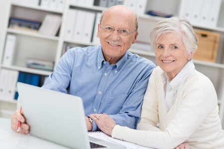 oldage: Senior couple working on a laptop in an office sitting close together as they share the screen and catch up on social media contacts