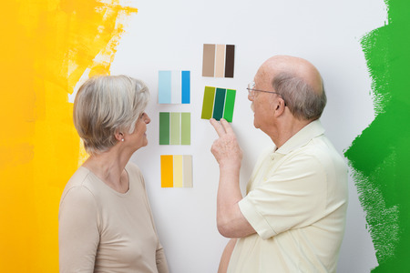Senior couple deciding on a new paint colour for their house looking at swatches on a wall on which they have already tested green and yellow paint