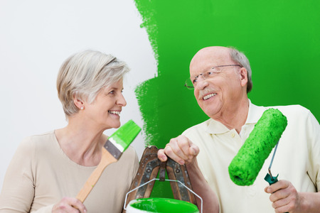 Happy senior couple painting their house green laughing as they dip their roller and brush into a large can of paint photo