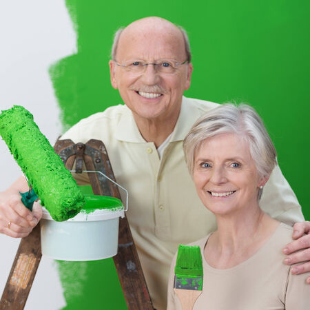 Smiling senior husband and wife team painting their new house a vivid shade of green photo