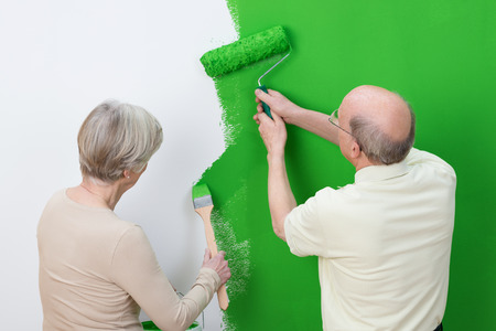 Senior couple renewing the interior decor painting the wall of their house a shade of bright green, view from behind photo
